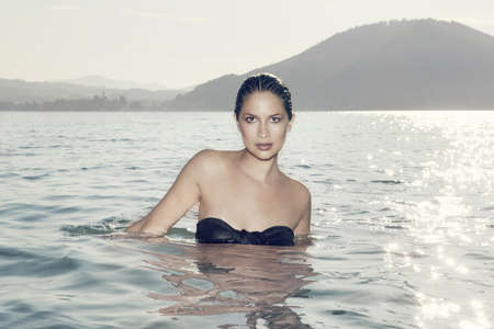 Portrait of sultry young woman standing in Lake Attesee, Austria