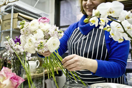 Floral designer preparing flowers in studio LANG_EVOIMAGES
