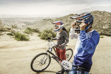 Male and female mountain bikers at race start line, Fontana, California, USA