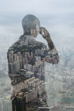 Businessman using smartphone and Hong Kong cityscape,composite image