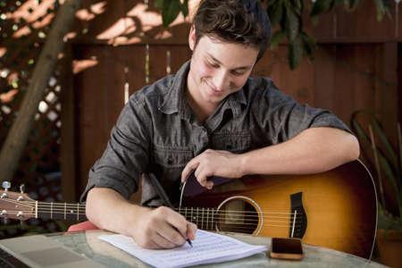 Young man composing music in garden
