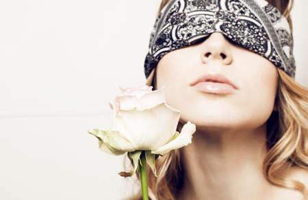 Model in blindfold with rose LANG_EVOIMAGES