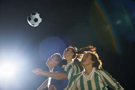 Female soccer players hitting ball with head