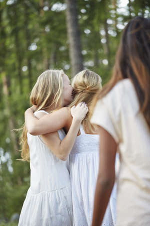 Teenage girls with arm around each other in forest