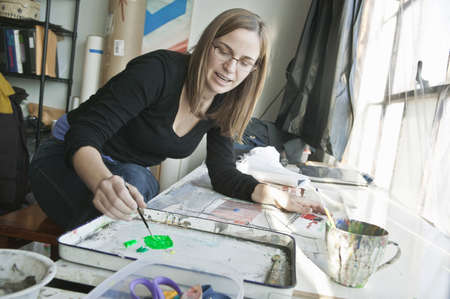 Female artist painting in studio LANG_EVOIMAGES