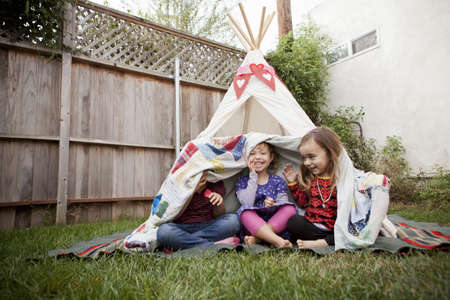 Three young girls in garden hiding under blanket