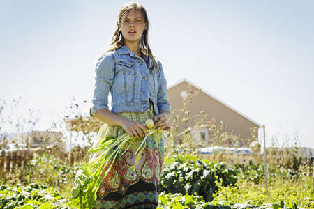 Portrait of young woman harvesting vegetables on farm