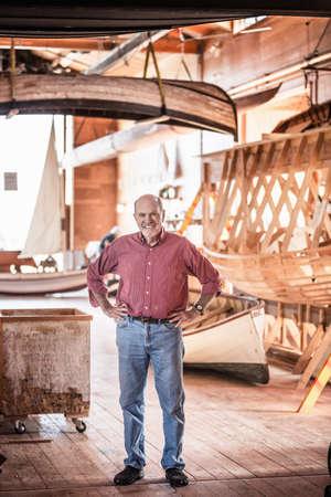 white wood floor: Senior man standing in boat-building workshop