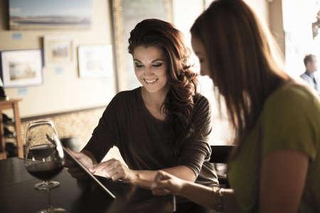 socialise: Businesswomen looking at digital tablet in a wine bar