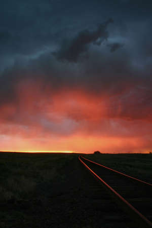 Intense sunset colors reflect off railroad tracks, Burlington, Colorado, USA