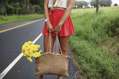 Woman with straw bag on roadside