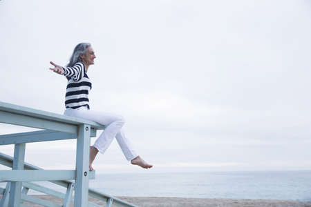 health equity: Mature woman sitting on seaview balcony at coast, Los Angeles, California, USA