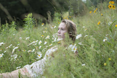 Teenage girl lying down on wildflowers