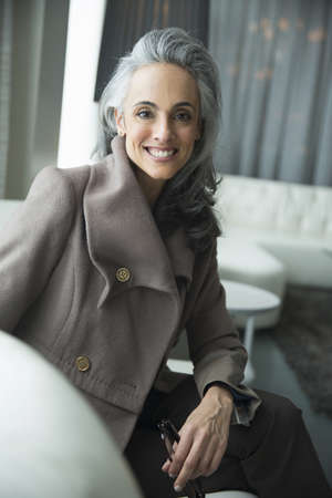 Portrait of mature woman on white luxury sofa LANG_EVOIMAGES