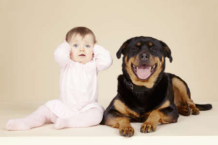 floor covering: Studio portrait of Rottweiler dog and baby girl with hands over ears LANG_EVOIMAGES