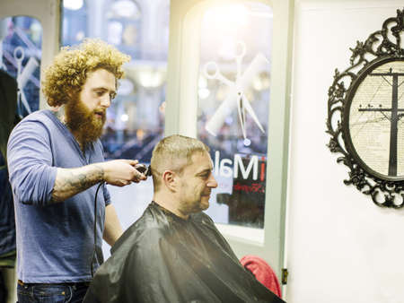 Barber cutting mature mans hair with clippers LANG_EVOIMAGES
