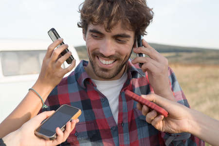 Young man on cell phone with hands holding smartphones