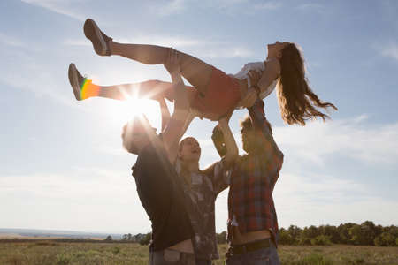 arms lifted up: Three friends lifting young woman above their heads