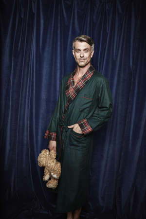 suave: Male entertainer in smoking jacket holding teddy bear LANG_EVOIMAGES