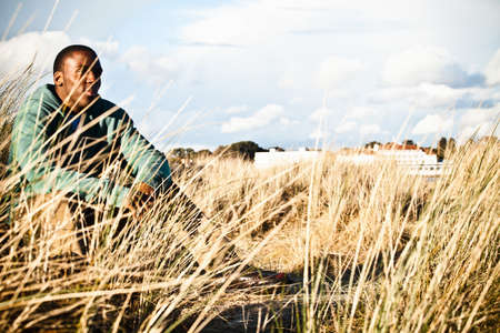 Young man sitting in sand dunes, Bournemouth, Dorset, UK LANG_EVOIMAGES