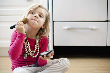 pyjama: Young girl sitting on kitchen floor with make up