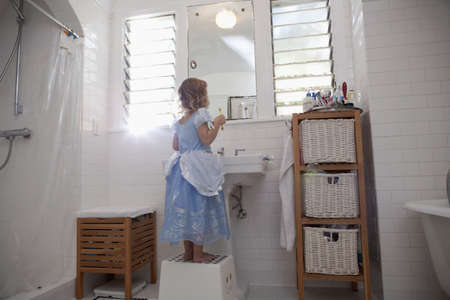 well behaved: Female toddler standing on step cleaning teeth