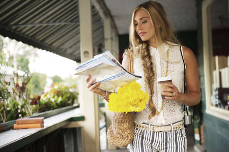 Young woman with map in verandah LANG_EVOIMAGES