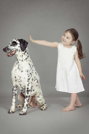 Studio portrait of female toddler and dalmatian dog