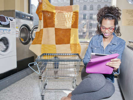 electronic organiser: Young woman in launderette using tablet and wearing headphones
