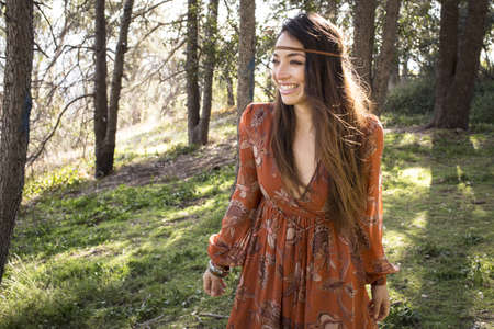alice band: Portrait of young woman wearing dress in forest, smiling LANG_EVOIMAGES
