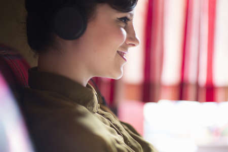 groovy: Young woman sitting on sofa, listening to music on headphones