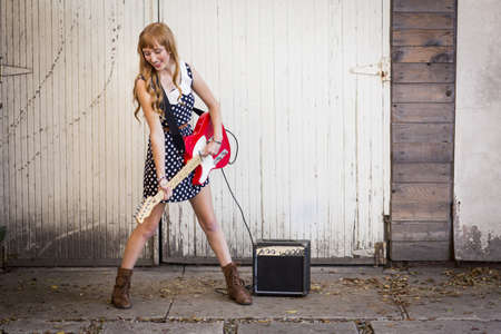 domestic garage: Young woman playing electric guitar outside garage