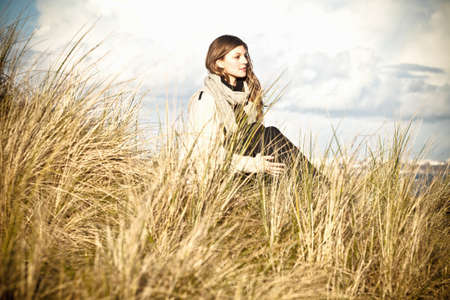 Young woman sitting in sand dunes, Bournemouth, Dorset, UK LANG_EVOIMAGES