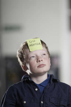 Portrait of boy with sticky note on forehead
