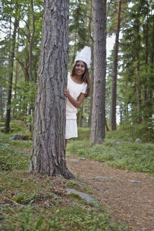 Teenage girl wearing white hat by tree in forest