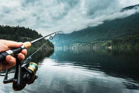 Man holding fishing rod close-up, Buntzen Lake, British Columbia, Canada