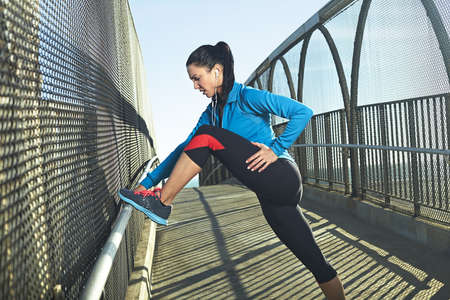 exerting: Mid adult woman stretching on bridge