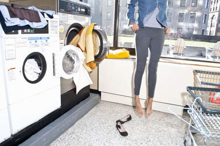Young woman in launderette, putting on freshly dried clothes
