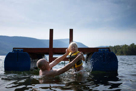 Father and toddler daughter playing in lake,Silver Bay,New York,USA