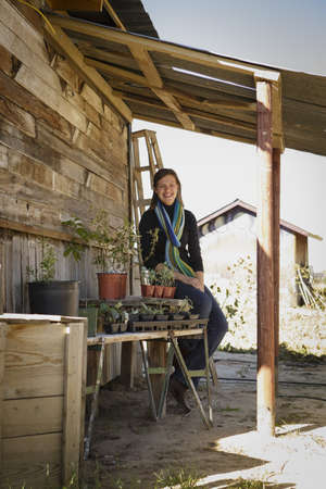 farmyards: Portrait of young woman growing plants