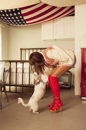 silliness: Woman wearing red knee-high socks bending towards dog