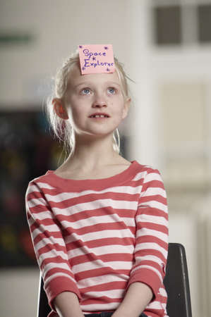Portrait of girl with sticky note on forehead
