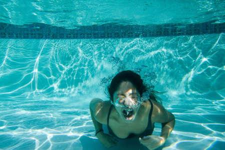 Joven mujer luchando bajo el agua LANG_EVOIMAGES