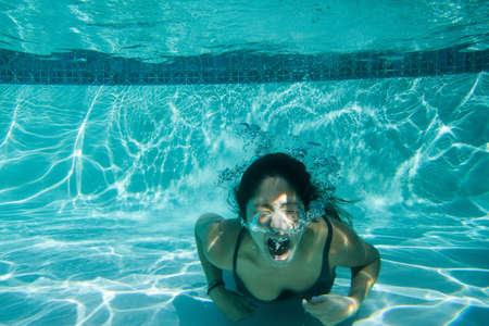 Young woman struggling underwater