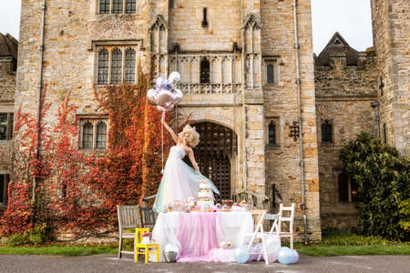 ceremonial make up: Bride standing on table outside castle, holding balloons