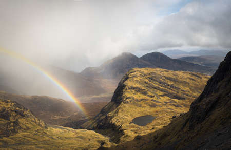 Passing storm, rainbow and mountain lake, Red Cuillin from Bla Bheinn mountain, Isle of Skye, Scotland