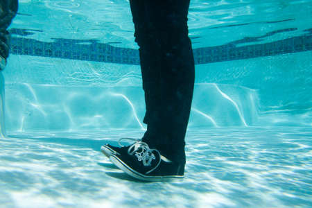 Young man in clothes standing underwater LANG_EVOIMAGES