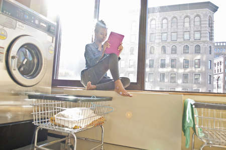 electronic organiser: Young woman using tablet in launderette, waiting for laundry to finish LANG_EVOIMAGES
