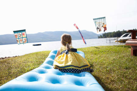 trouble free: Female toddler crouching on air bed,Silver Bay,New York,USA