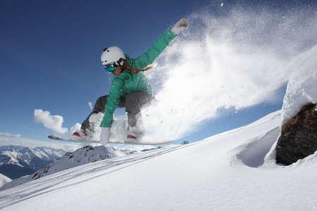 Young woman jumping on snowboard, Mayrhofen, Tyrol, Austria